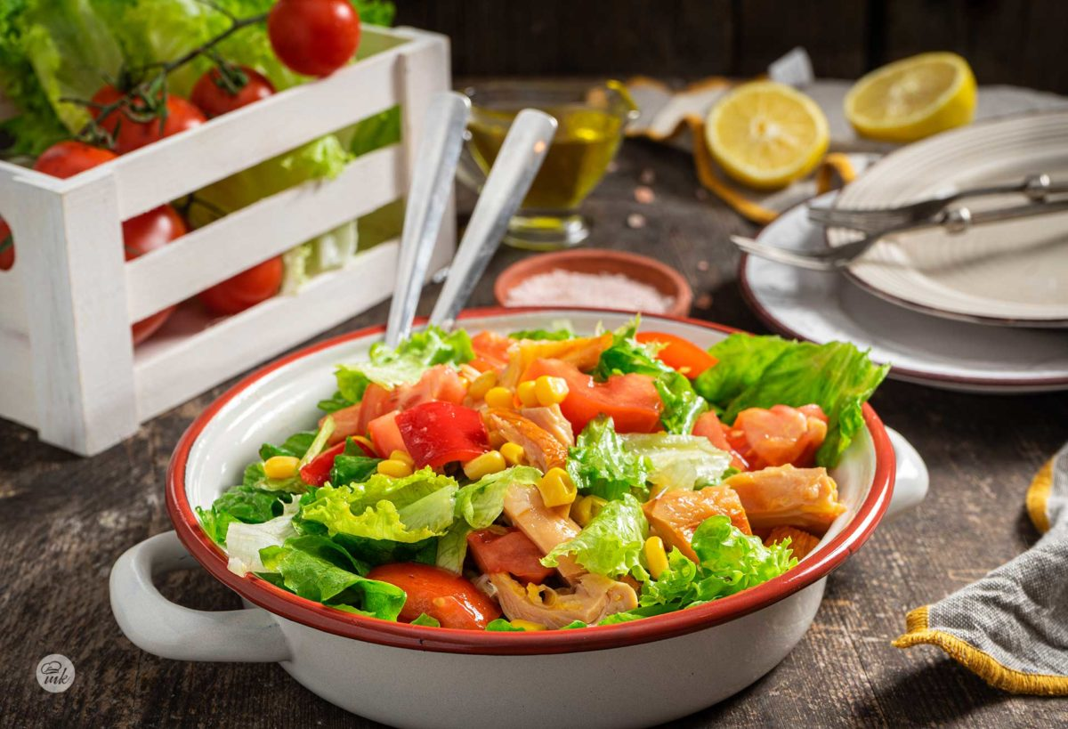Зелена салата с пушено пиле, сериварана в купа, две чинии отстрани, сол, лимон, чери домати, снимано отстрани