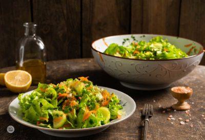 Свежа салата, сервирана в чиния и голяма купа с лимон, зехтин и сол, снимана отстрани
