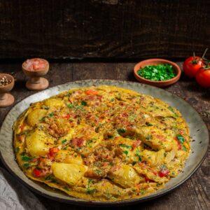Омлет по селски, серивиран в чиния с магданоз, шарен пипер, сол, чери домати, снимано отстрани