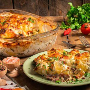 Картофи със сметана, бекон и топено сирене, сервирано в чиния и прозрачен съд, със сол, шарен пипер, чери домати и магданоз, снимано отстрани