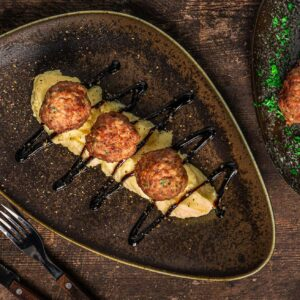 Кюфтета по цариградски, сервирани в чиния с картофено пюре и сос, снимани отгоре