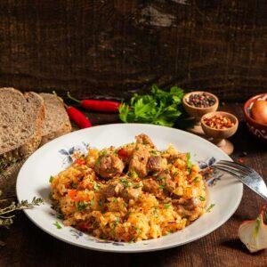 Славянски гювеч, поднесен в порция в чиния, аранжиран с пресни подправки и филии хляб