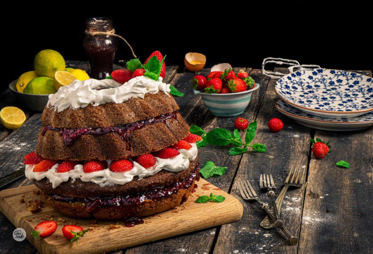 Кекс с мармалад заснет отстрани, поднесен на тавичка и декориран със сметана и пресни ягоди
