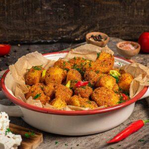 Пикантни картофи, поднесени в чиния, с люти чушки и сирене, снимани отстрани