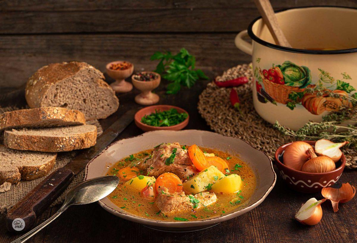 Свинска яхния със зеленчуци, поднесена в чиния, аранжирана с пресни подправки и заснета отстрани