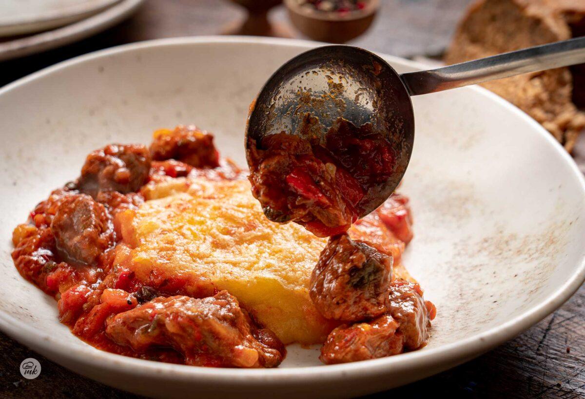 Порция телешко с домати и печено пюре в бяла чиния, снимано отпред