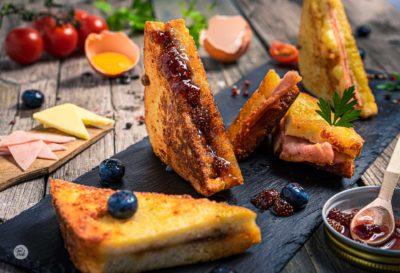 Пържени пълнени филийки с шунка и топено сирене заснети в близък кадър, декорирани със сладко от горски ягоди