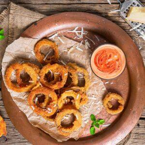 Лучени кръгчета, заснети отгоре, поставени в чиния и поднесени със сос