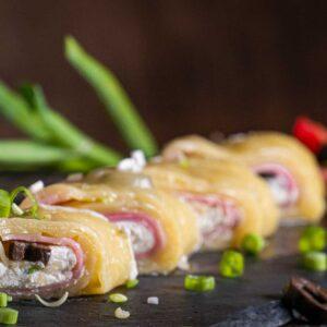 Кашкавалено руло с шунка и сирене Крема, заснето отблизо и декорирано с пресни подправки