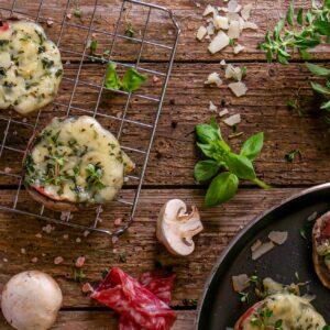 Печурки на скара с пепероне и сирене, заснети отгоре и артистично поднесени на решетка, декорирани с подправки