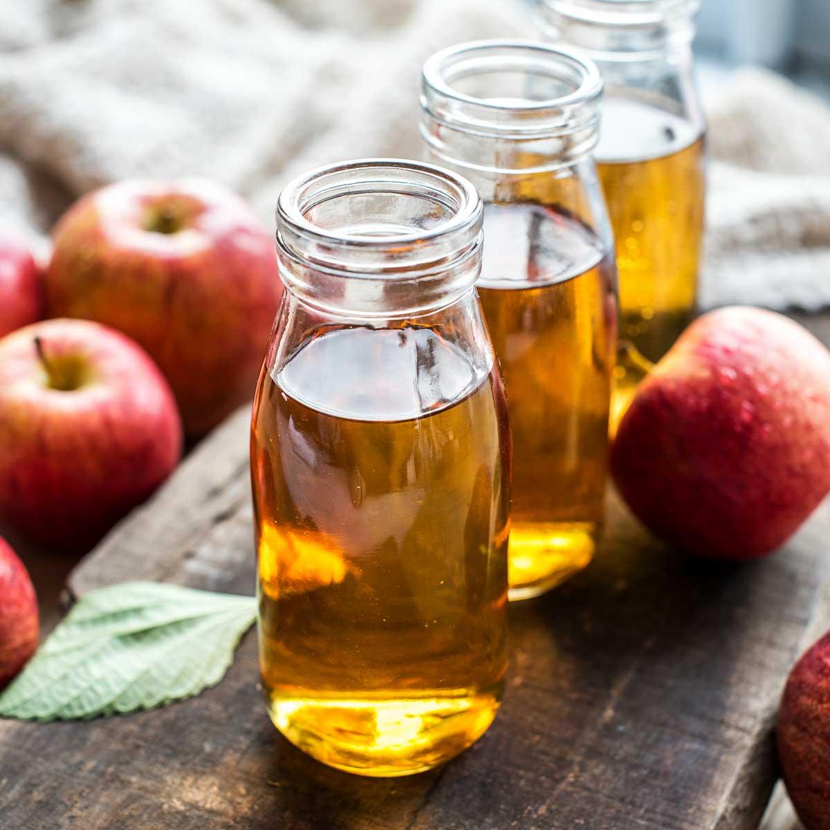 Домашен ябкълков оцет и ябълки върху дъска за рязане