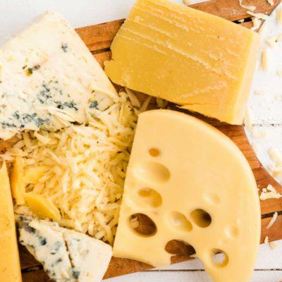 Чедър, маасдам, синьо сирене и кашкавал на дървена дъска за рязане