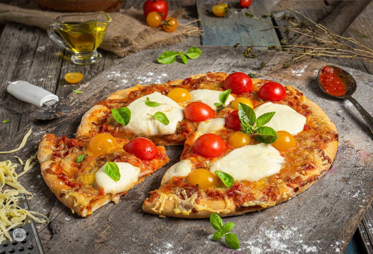 Пица с шунка и кашкавал, моцарела, чери домати и пресен босилек, заснета отблизо на стара дървена маса
