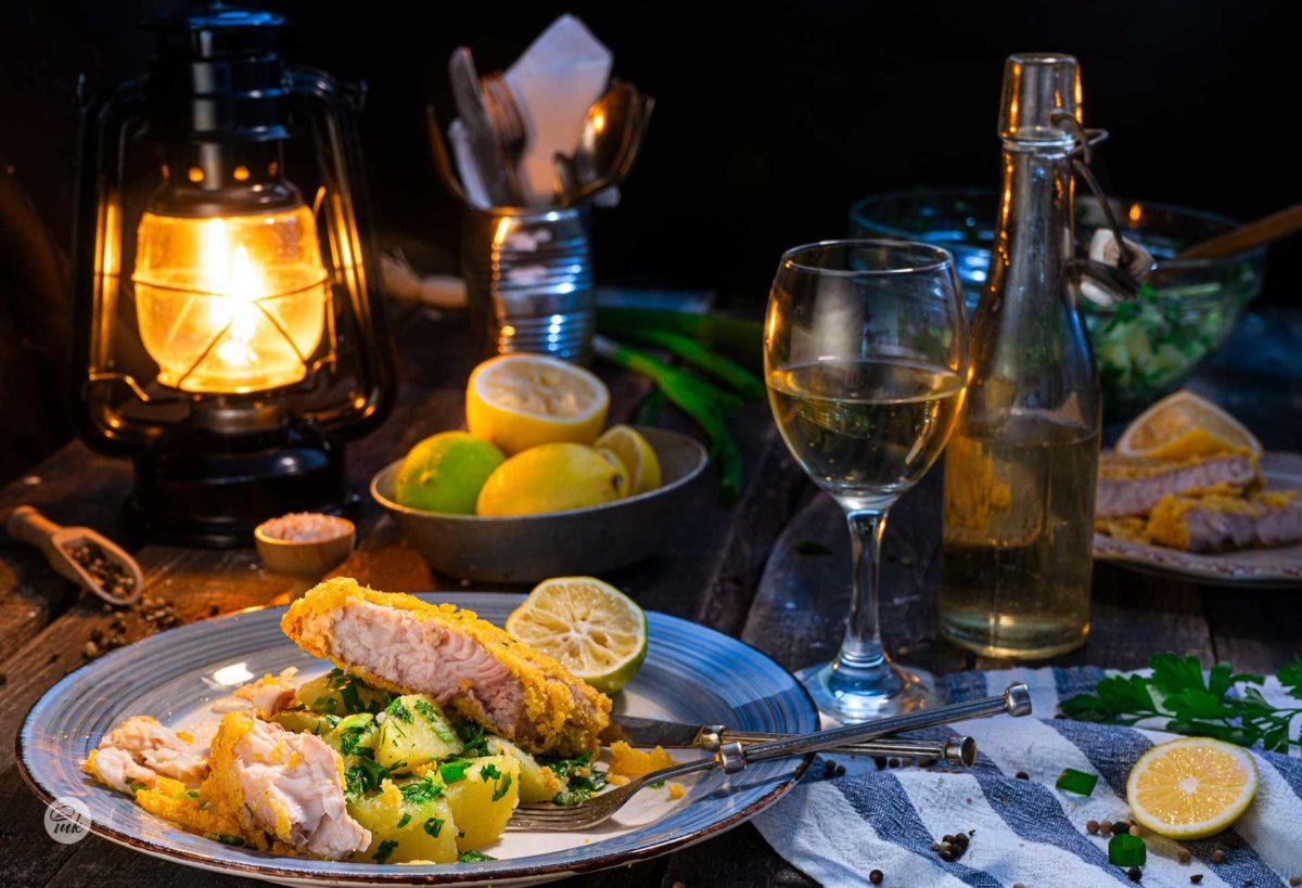 Пържен сом с картофи, поднесен на романтична вечеря с чаша бяло вино