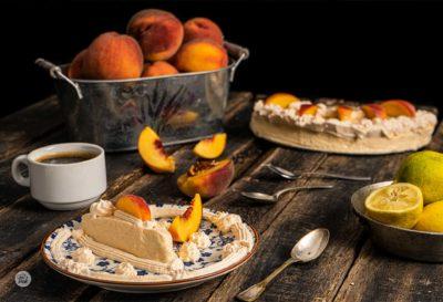 Парфе от праскови заснето отстрани, поднесени със кафе и пресни плодове