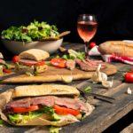 Телешки стек сандвич заснет отстрани, поднесен с чаша вино