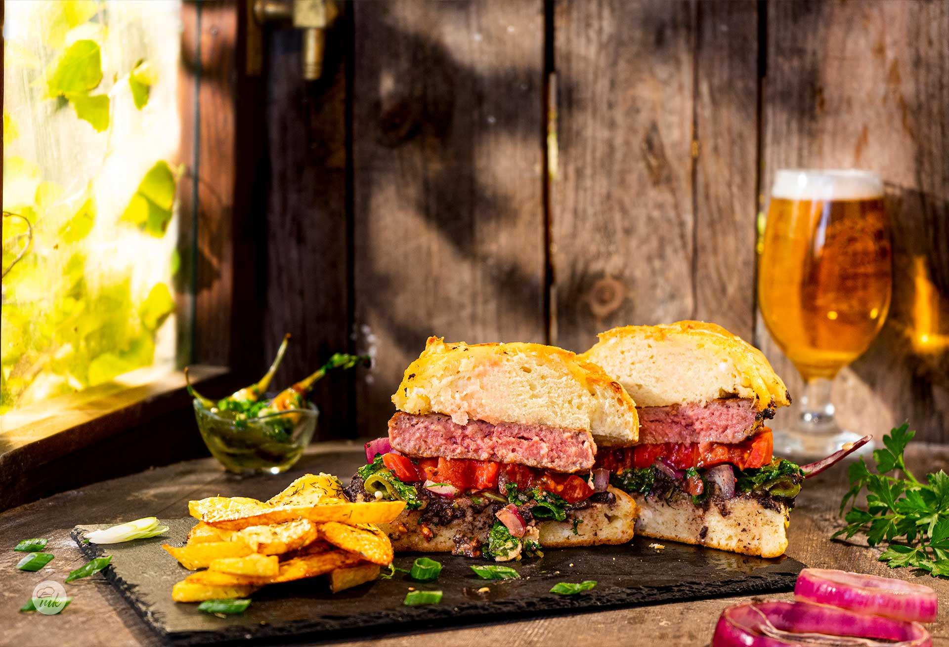 Телешки бургер поднесен с пържени картофки и люти чушлета, срязан на две и заснет отстрани