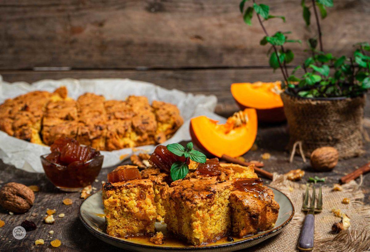 Сладкиш с тиква и стафиди, поднесена в чиния с мента, тиква, рачел, орехи и канелени пръчици, снимано отстрани