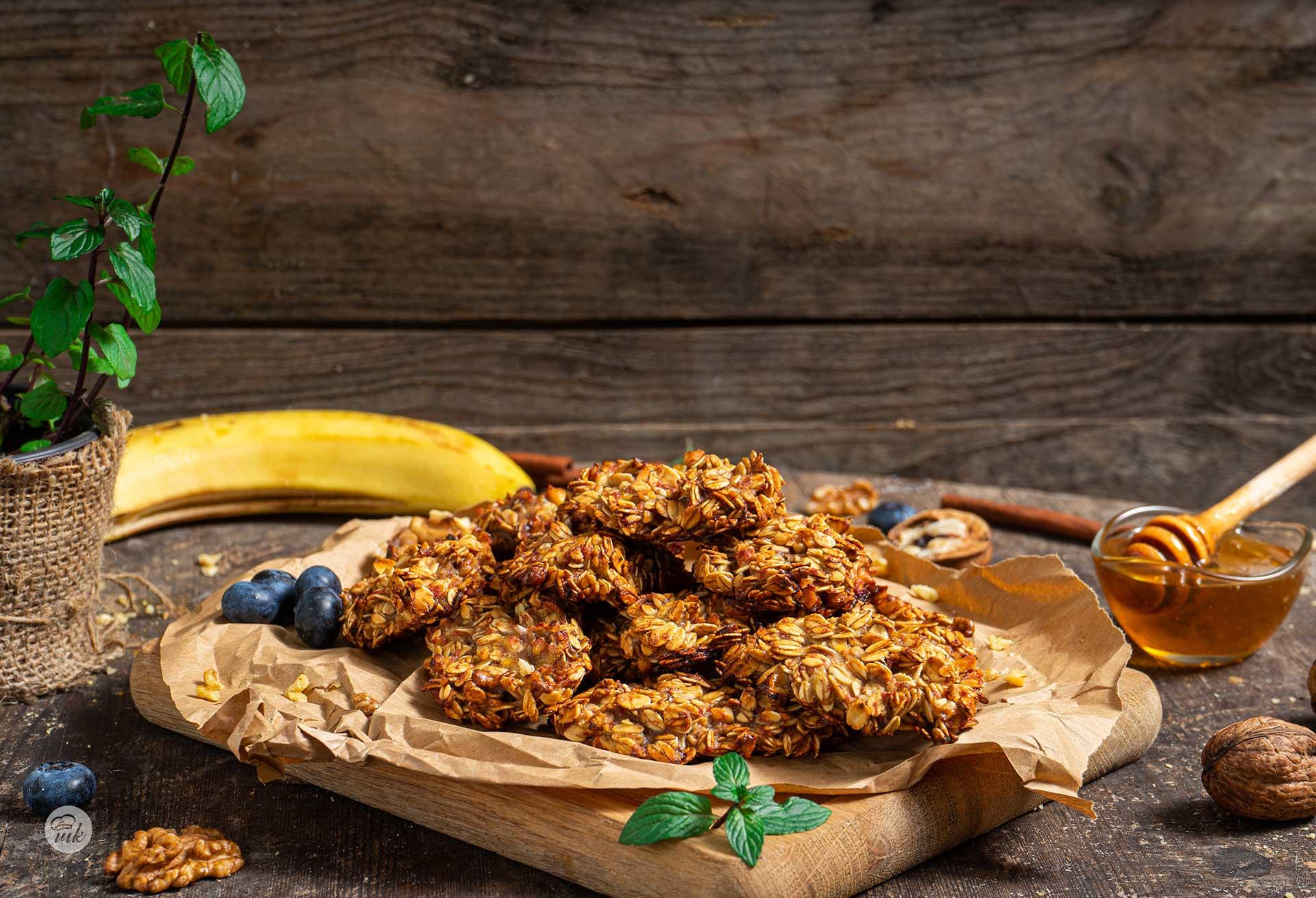 Бананови бисквити, поднесени на дъска с хартия за печене и боровинки, снимани отстрани