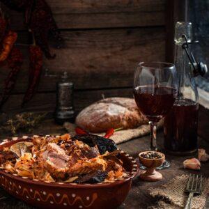 Кисело зеле със свинско и пушена сланина, сервирано в глинен съд, на заден фон с хляб и червено вино, снимано отстрани