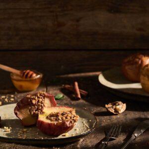 Печени ябълки, сервирани в чиния с орехи, канела, мед, снимани отстрани,