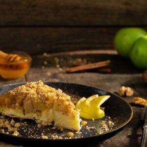 Ябълкова тортар сервирана в чиния с натрошени орехи, мед, ябълки на заден фон, снимано отстрани