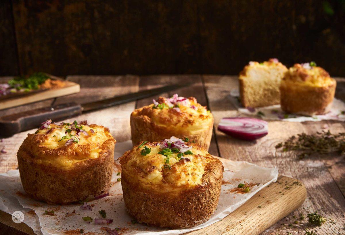 Мини кексчета с яйца и сирене, снимани на дъска върху хартия за печене с червен лук, снимано отстрани