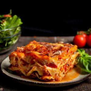 Лазаня Болонезе с телешка кайма, сервирана в чиния с босилек, салата и чери домати на заден фон, снимана отстрани