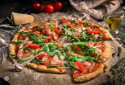 Пица с прошуто и рукола, поднесено на хартия за печене с чери домати, зехтин и мащерка, снимано отстрани