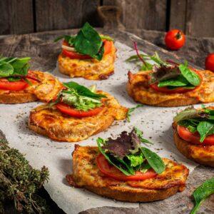 Принцеси с шунка и кашкавал, сериврани на хартия за печене със салата и чери домати, снимано отстрани