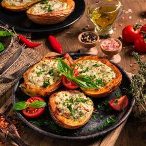 Пълнени картофи с извара, сервирани в черни чии с чили, босилек, чери домати, люти чушки, сол и зехтин, снимани отстрани