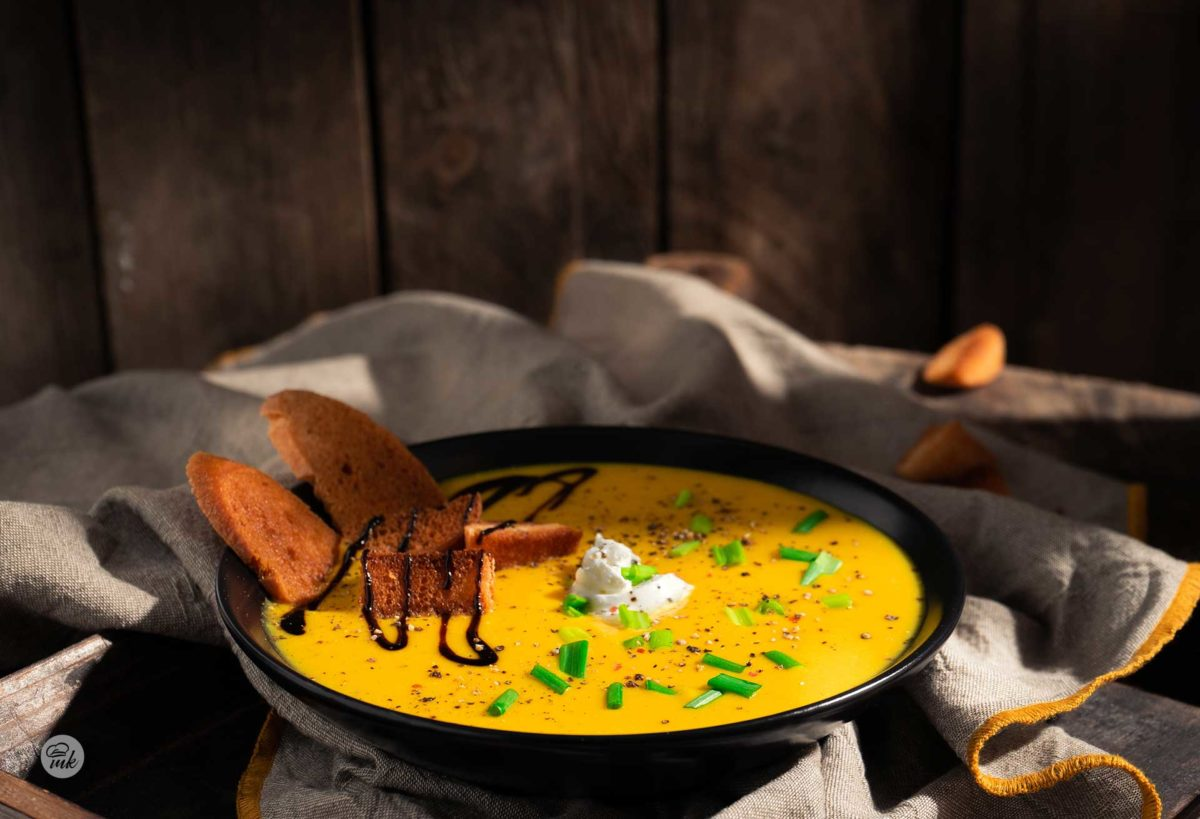 Крем супа от картофи и праз, сервирани в черна купа с брускети, сметана и сос, сниман отстрани