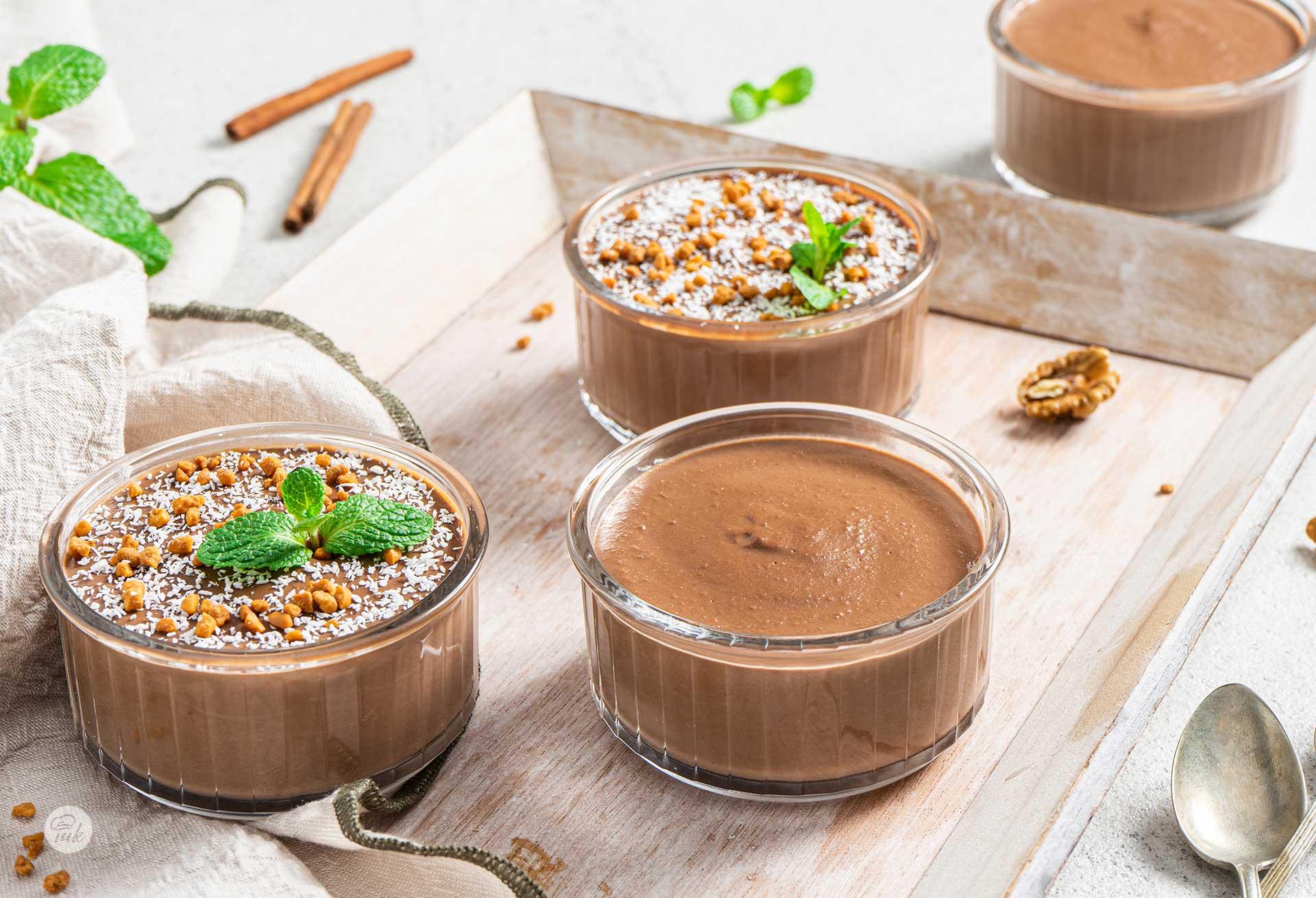 Шоколадов крем, сервиран в три прозрачни купички, две от тях с мента, кокосви стърготини, канелени пръчици, снимани отстрани