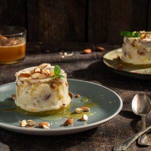 Кисело мляко с ананас и бадеми, сервирано в синя чиния с мед, мента и натрошени бадеми, още една чиния и купчка мед, снимано отстрани