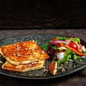 Кашкавал на плоча, сервиран в черна чиния със салата за гарнитура, снимано отстрани