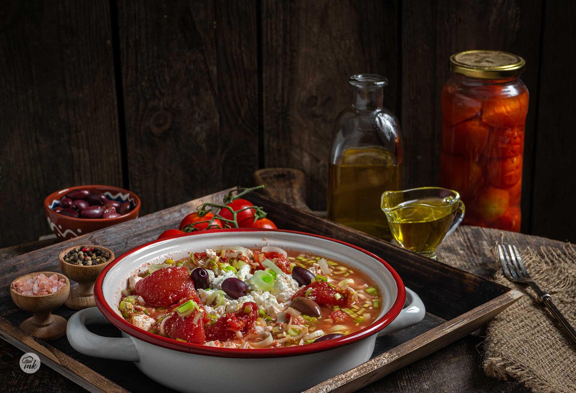 Салата от консервирани домати и праз, сервирана в дълбока чиния, с чери домати, зехтин, буркан домати, маслини, сол и шарен пипер, снимана отстрани