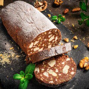 Сладък салам, на черна дъска, с отрязани две парчета, поръсен с пудра захар, мента и орехи и обикновени бисквити, сниман отстрани