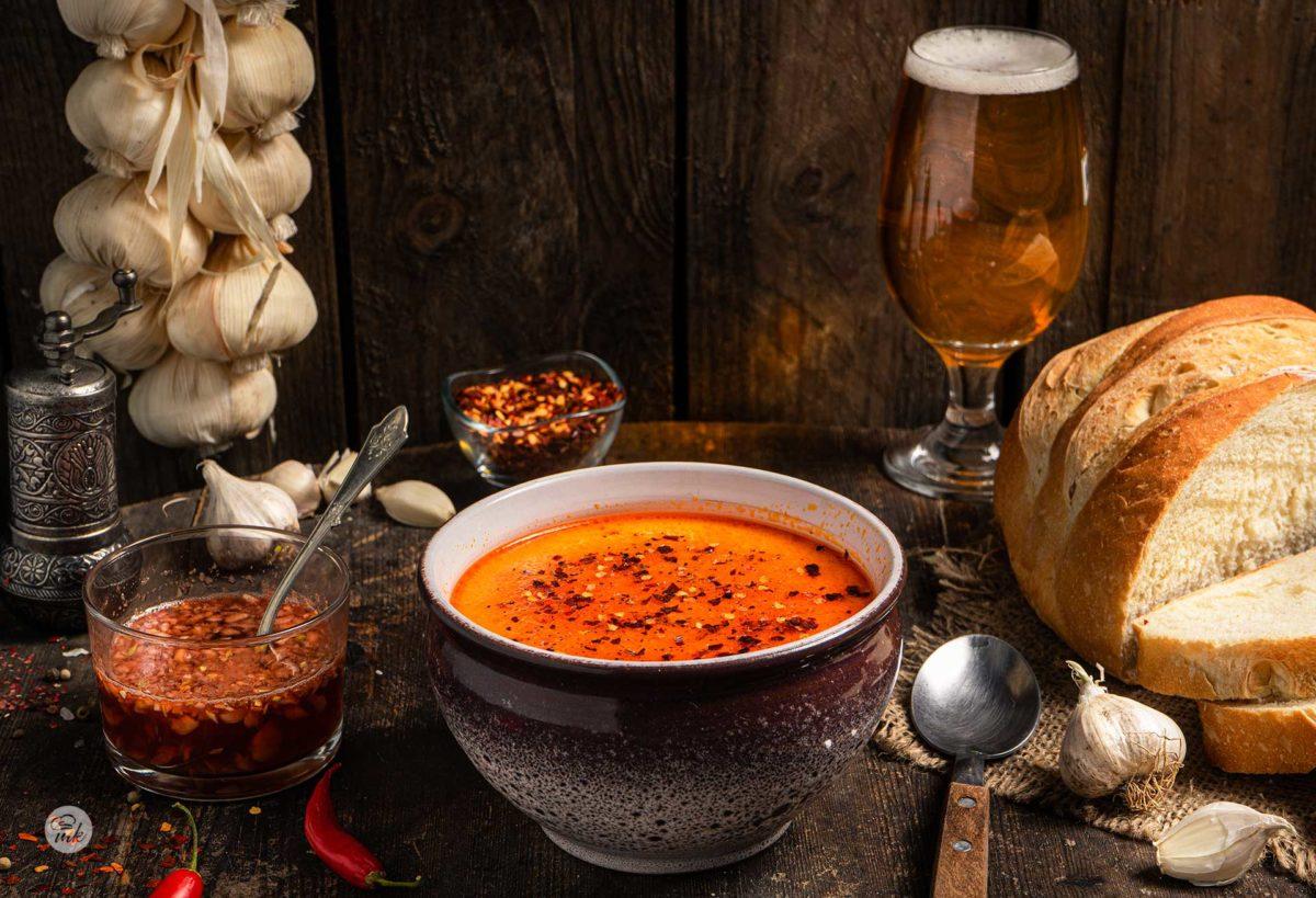 Шкембе чорба, сервирана в купа с чесън, чили, чаша бира, хляб, лъжица и скилидки чесън, снимана отстрани