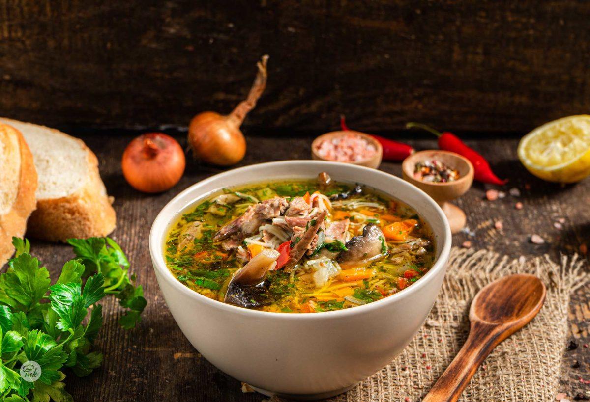 Бистра патешка супа, сервирана в купа с лук, лимон, сол, шарен пипер, хбяб, лютии чушки, снимана отстрани