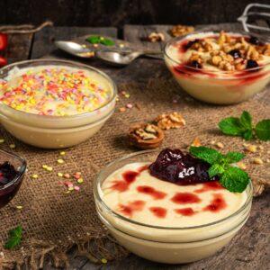 Крем ванилия поднесен в три купички с три различни предложения за топинг: захарни пръчици, сладко от вишни и мед и орехи