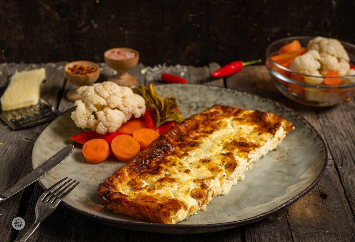 Настърган кашкавал на фурна, сервиран в чиния с туршия, люти чушки, сол, снимано отстрани