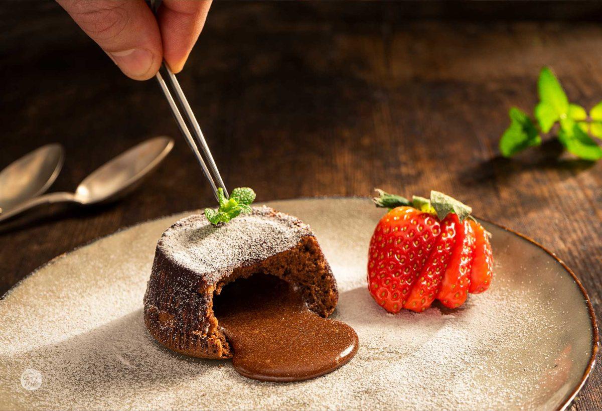 Шоколадово суфле, сервирано в чиния с пудра захар, ягоди и листенце мента, снимано отстрани