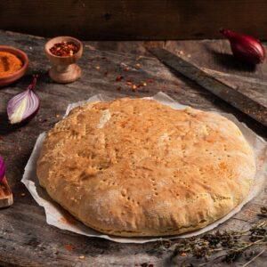 Бърза содена питка, сервирана на хартия за печене с червен лук, шарена сол, снимано отстрани