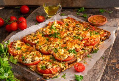 Филии с домати на фурна, сервирани върху хартия за печене, снимани отстрани