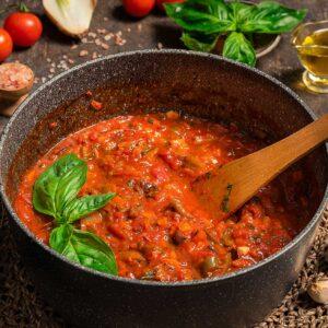 Доматен сос за паста, сервиран в тенджера с босилек, зехтин, снимано отстрани