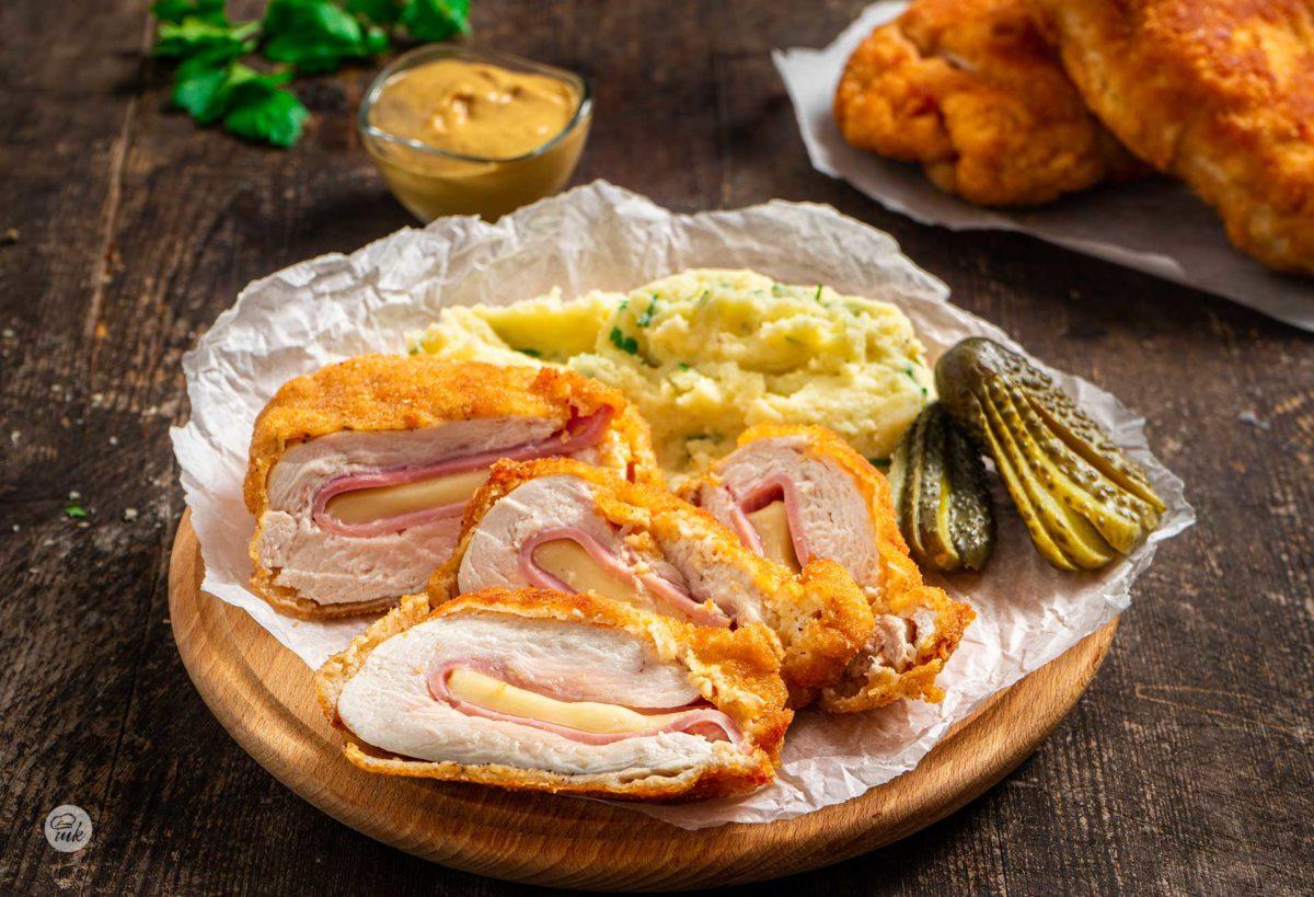 Кордон бльо с пилешко филе, сервирано върху хартия за печене с кисели краставички, картофено пюре, горчица, снимано отстрани