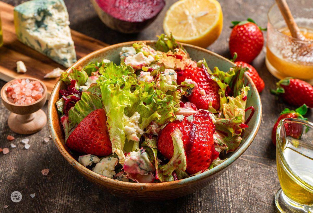 Зелена салата със синьо сирене и ягоди, поднесена в купичка и аранжирана с пресен лимон, зехтин и подправки
