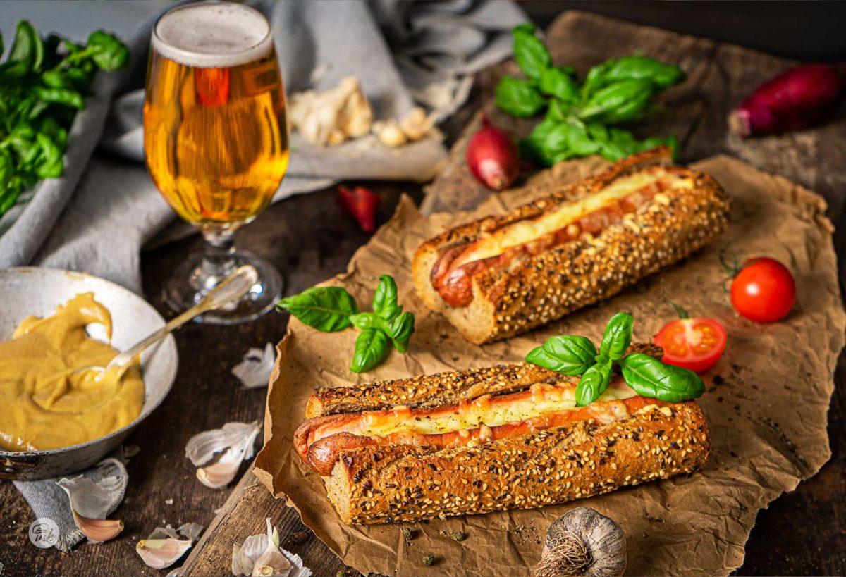 Чеснов хотдог в багета с кашкавал, поднесен с бира и декориран с пресен босилек и чери домати