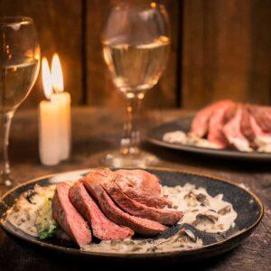 Филе от патица със синьо сирене, сметана и орехи, подредено във формата на ветрило и поднесено в бяло вино на светлина от свещ