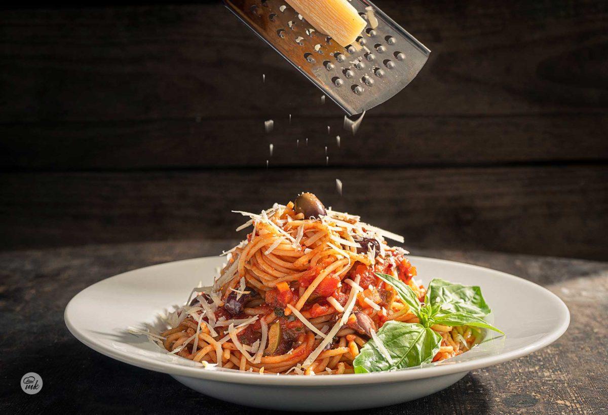Спагети с доматен сос, сервирани в бяла чиния, ръсейки пармезан, снимано отстрани